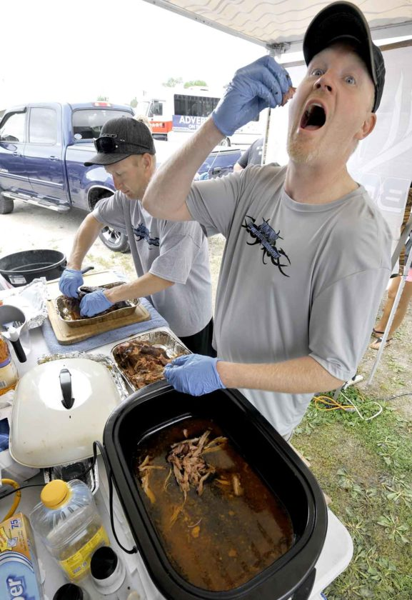 -Messenger photo by Hans Madsen  Ryan Friesth, of Fort Dodge, a member of the Bonehead Barbecue team, samples some of their pulled pork during a previous Badgerfest. They were preparing for judging at the BBQ Battle at the Badger Fest. His fellow team member, Dan Davis, worked at left.