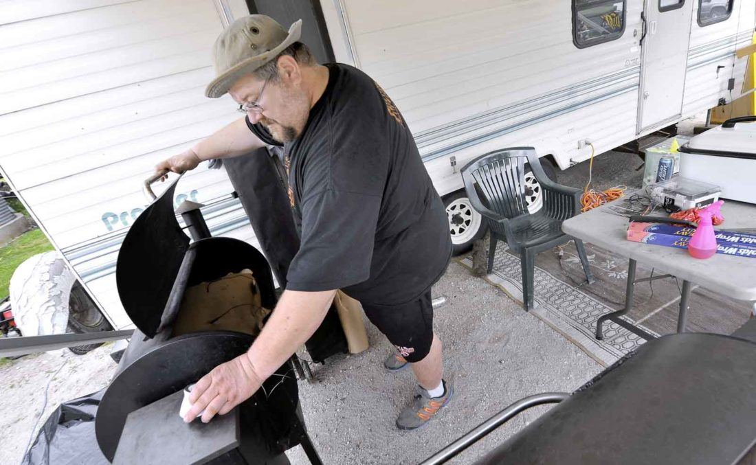 -Messenger photo by Hans Madsen  Anthony Johnson, of Fort Dodge, checks the temperature of his chicken during the BBQ Battle of a previous annual Badger Fest. Johnson spent most of the night staying awake to keep an eye on his slowly cooking food.