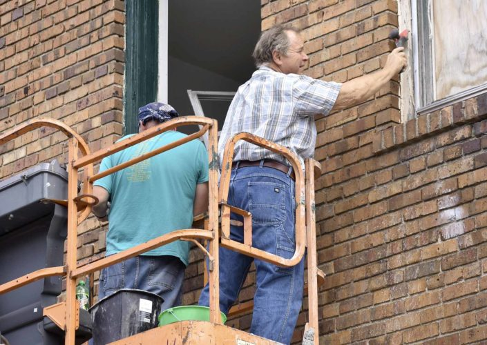 -Messenger photo by Chad Thompson  Larry Bickford, of Fort Dodge, scrapes some of the old paint off of a window frame at 1100 Central Avenue recently. The three-story building was damaged by the storm on May 16.