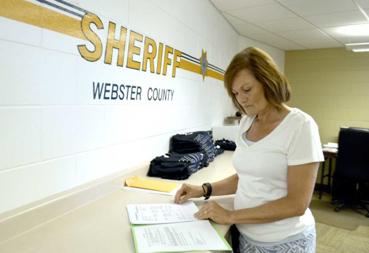 -Messenger photo by Peter Kaspari  Roxanne Leadley, a civil clerk with the Webster County Sheriff's Department, goes over some paperwork.