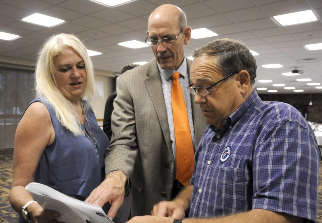 -Messenger photo by Joe Sutter  Lori Davis, public relations, Iowa Insurance Commissioner Doug Ommen, and Bob Singer of Fort Dodge, look over the information packet provided at the Fraud Fighters Forum Wednesday. Singer had already taken some of the advice offered that day to protect his credit.