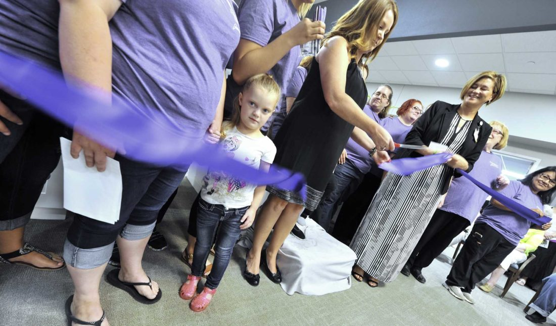 -Messenger photo by Hans Madsen  Kennedy Irwing, 4, doesn't know quite what to make of all the activity around her Thursday afternoon as she stands with her mom, caregiver Jessica Irwing, during the ribbon cutting for the Journeys at Friendship Haven. Unit director Allison Zuspan, cuts the ribbon as Friendship Haven President/CEO Julie Thorson, holds onto the end at right. The first residents of the memory care center will move in Tuesday.