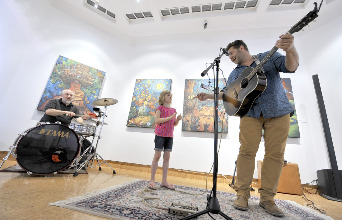 "-Messenger photo by Hans Madsen  Musician, painter and children's book author Chad Elliott, of Lamoni, at right, gets a little help from Sadie Shields, 6, of Fort Dodge, as he performs one of the songs from his album ""Wilderman's Treetop Tales"" at the Blanden Memorial Art Museum Thursday afternoon. The paintings on the wall were all done by Elliott and served as the inspiration for the book and album. Jim Van Dorn, of Stuart, plays drums at left. Elliott has several other albums of music to his credit including his newest CD ""Wreck and Ruin."" About 50 people attended the free show."