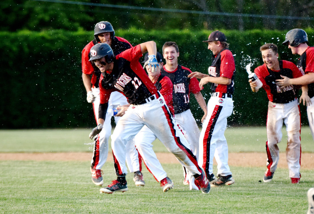 -Messenger photo by Britt Kudla Tyrman Lara of Fort Dodge gets drenched as he runs away from his teammates after driving in the winning score, giving the Dodgers a 6-5 victory over Roosevelt on Thursday