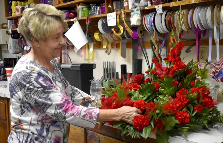-Messenger photo by Chad Thompson  Betty Wilde, an owner of the Eagle Grove Greenhouse, prepares a flower arrangement at the greenhouse.