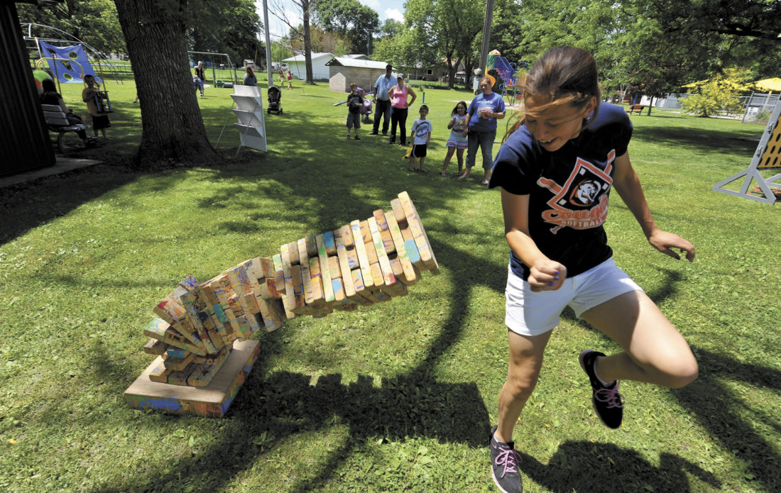 -Messenger file photo Samantha Ruhland, 14, of Clare, dodges out of the way as the giant game of Jenga she was playing comes to a crashing end during the games in the park at the 2015 Manson Greater Crater Days.