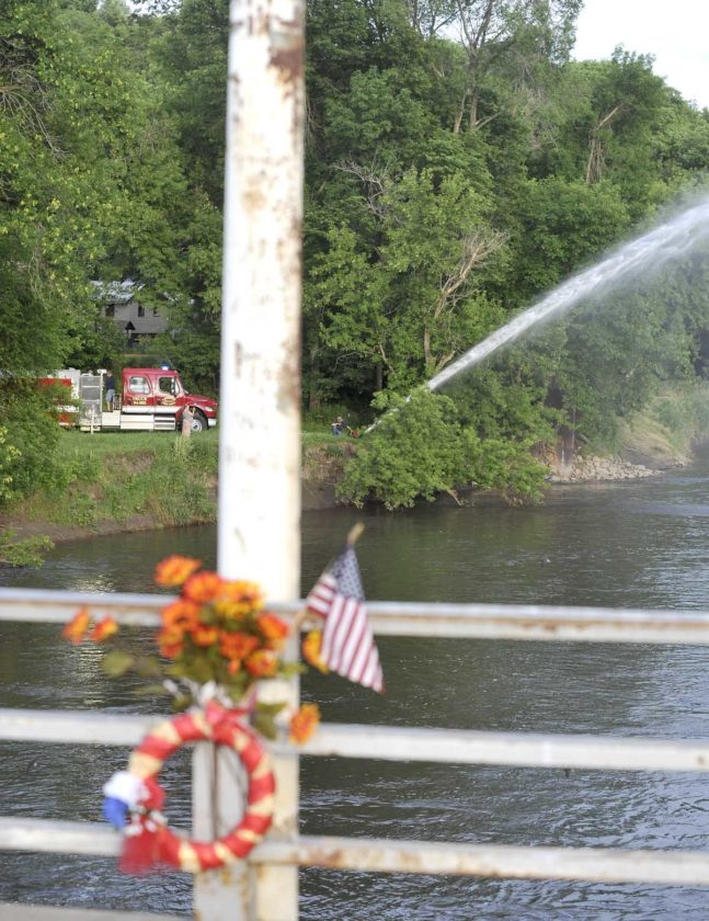 -Messenger photo by Hans Madsen  Framed by a flower arrangement left on the Des Moines River Bridge in Lehigh, members of the Lehigh Fire Department use their pumper truck to spray a water salute for Dayton Firefighter Colin Murphy Saturday night during a memorial service honoring him. Murphy drowned in the river on June 19, 2016 while swimming with friends. A Dayton Fire Department pumper truck also sprayed a salute from the opposite bank.