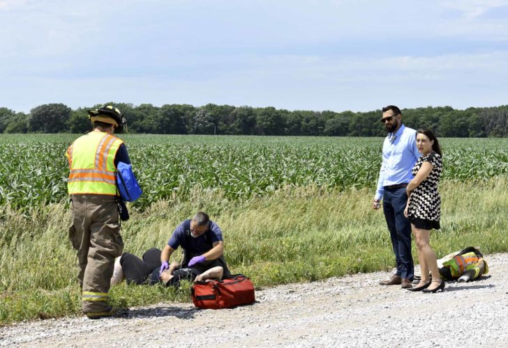 -Messenger photo by Chad Thompson  Nick Greb and Cheyene Robertson, of Des Moines, at right, look on after helping to rescue a woman involved a single-vehicle rollover crash on National Avenue Wednesday afternoon. Greb broke out a window in the vehicle and helped get the woman out, according to Lt. Kevin Kruse, of the Webster County sheriff's office.