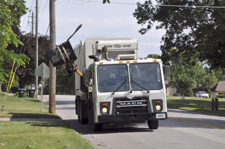 -Messenger photo by Peter Kaspari  A Fort Dodge sanitation truck lowers a garbage can after dumping its contents into the back. A new law, taking effect July 1, will require drivers passing sanitation and recycling vehicles to slow down or they will receive a citation.