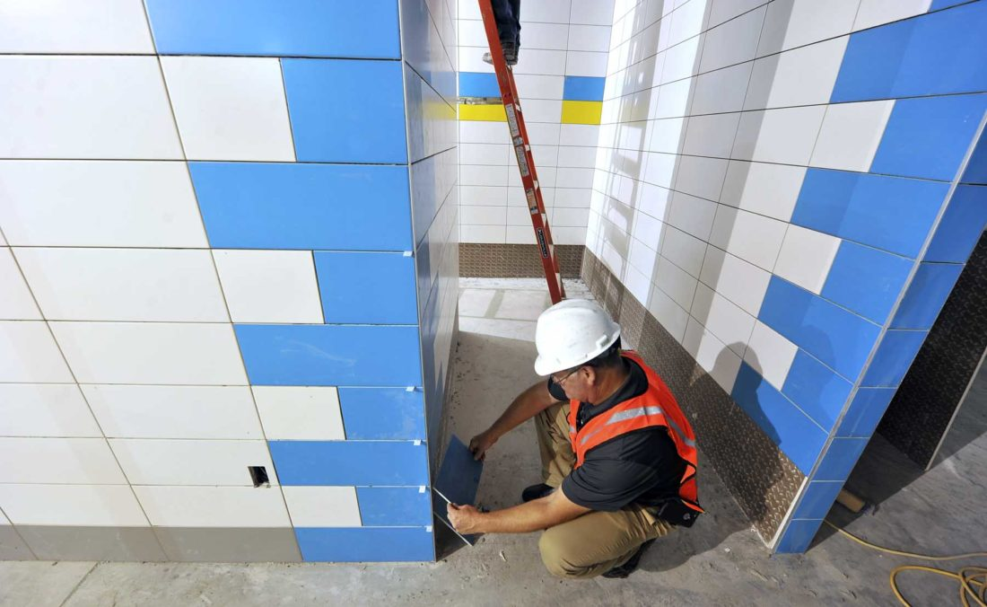 -Messenger photo by Hans Madsen  Travis Filloon, director of buildings and grounds for the Fort Dodge Community School District, looks over some of the recently completed tile work inside the new Duncombe Elementary School building.
