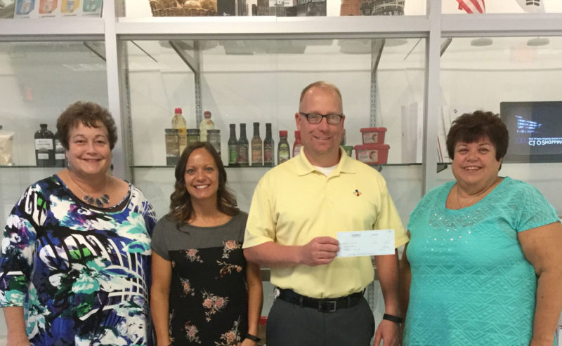 Lucas Palmer, with CJ Bio America, presents the title sponsor check to Barbara Michaels of Badger Lake Dragon Boat Association for the CJ Bio America Dragon Boat Bash Aug 11-12. Pictured from left are Linda Donner, Heather Farrell, Palmer and Michaels.