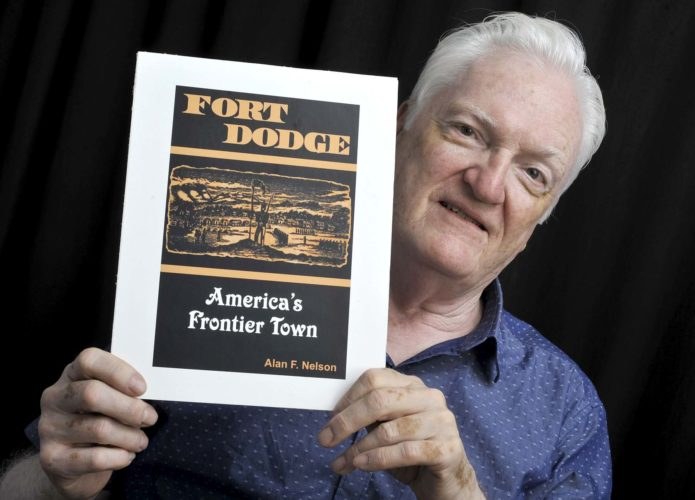 -Messenger photo by Hans Madsen  Fort Dodge historian Al Nelson holds up a print of one of the designs he's considering for the cover of the book he's working on about the history of Fort Dodge during the Frontier Era.