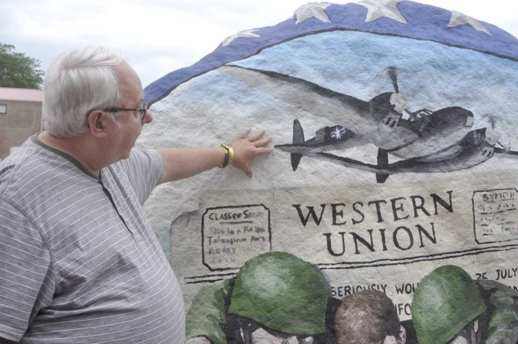 -Messenger photo by Peter Kaspari  Steve Gerry, of Sac City, explains the design on the Sac County Freedom Rock, located in downtown Sac City. Gerry, himself a United States Army veteran, helped bring Sac County's Freedom Rock to the city.