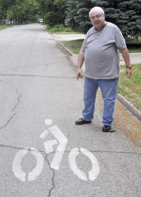 -Messenger photo by Peter KaspariSteve Gerry, of Sac City, poses next to a street marker cautioning drivers of bicyclists. Gerry, a member of the city's trails committee, recently helped get the street signs painted throughout Sac City.