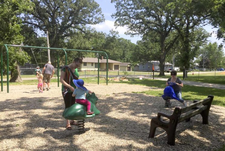 -Submitted photo  Rachel Tell Sasek, of Ames, watches as her daughter, Lydia Tell Sasek, 1, enjoys her time on the frog that's part of the new playground equipment in the Lehigh Park. Catie Tell, of Des Moines, checks out the whale, at right.