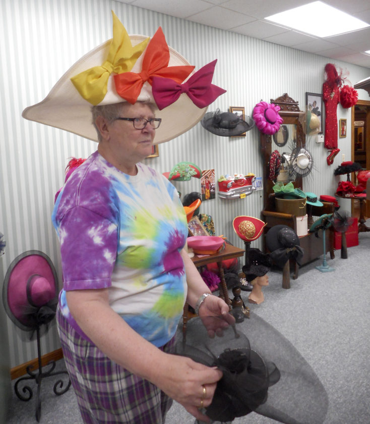 -Messenger photo by Karen Weld  Mary Tesdahl tries on one of the many hats housed in the Alvina Sellers' Iowa's Hat Lady portion of Clarion's Heartland Museum. Sellers was Tesdahl's husband's aunt.