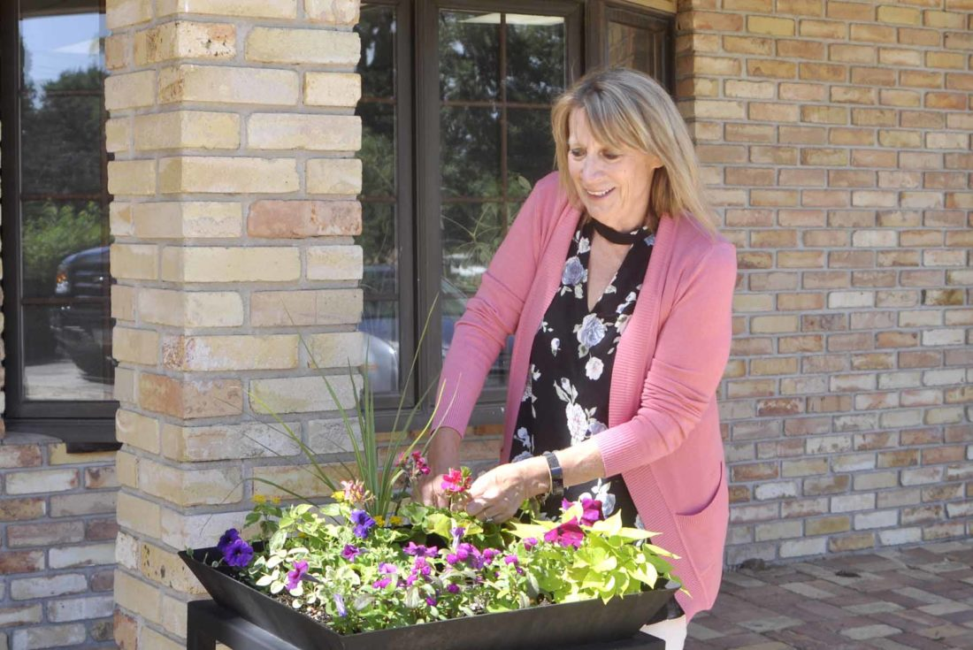 Joan Meyer, accountant at Cornwell, Frideres, Maher, & Associates. P.L.C, makes sure the flowers outside the office are healthy and beautiful.   - Messenger Photo by Hailey Brueschke