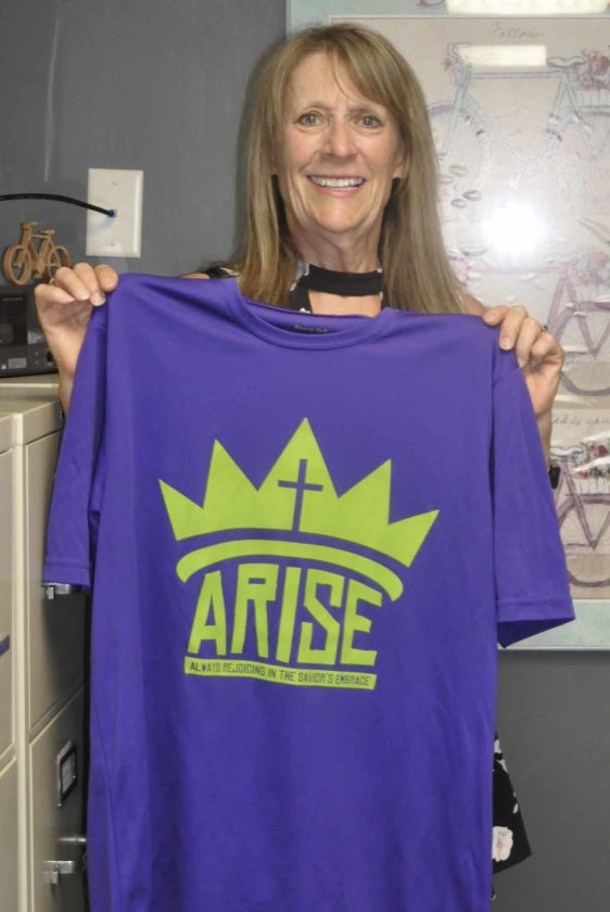Joan Meyer holds up Grace Lutheran Church's, ARiSE, high school youth group, new t-shirts for their upcoming mission trip. 
