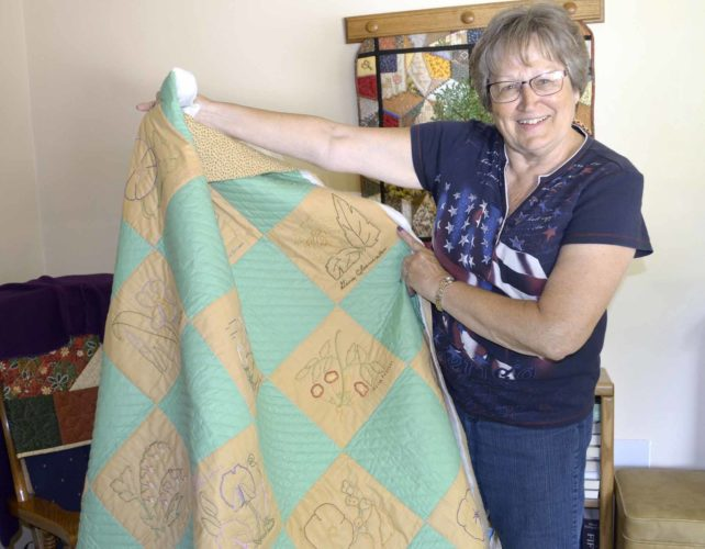 -Messenger photo  by Kriss Nelson  Rita Kail, of Farnhamville, displays a quilt she's working on that will be donated to the Farnhamville Betterment Building Committee. The quilt will become part of a fundraiser for the group.