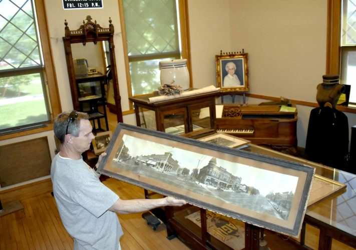 -Messenger photo by Chad Thompson  Ron Mohr, president of the Eagle Grove Museum board, holds a framed picture of downtown Eagle Grove from 1907 at the museum recently.