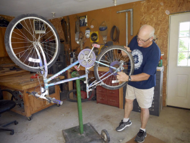 -Messenger photo by Karen Weld  Brian Ring works on upgrading a bike which had been abandoned in a shed, so it can be given to a new owner and rider.