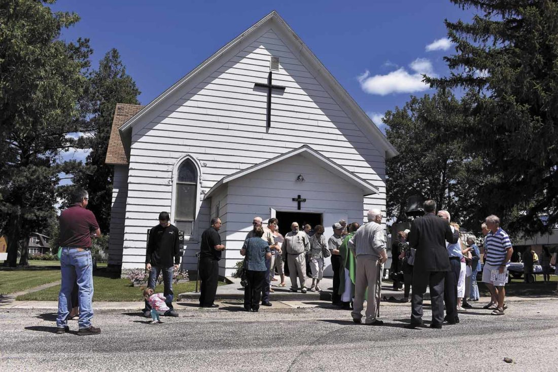 -Messenger photo by Chad Thompson  Members of St. John's catholic church gather outside after a farewell mass at the church Sunday.