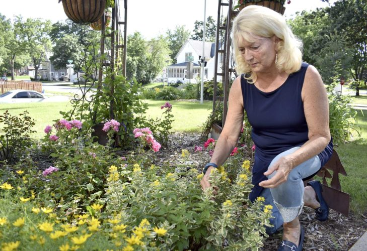 -Messenger photo by Chad Thompson  Skip Thompson, of Fort Dodge, kneels in one of her flower gardens at her home, 701 Crest Ave., recently. Her gardens are part of the Fort Dodge Federated Garden Club annual tour of gardens July 7.