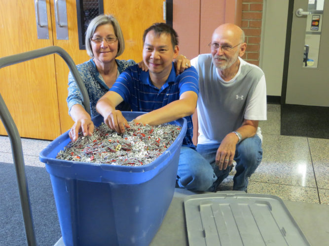 Brad Anderson (center) donated a tub of pop tabs he collected to the Fort Dodge Community School District's Rachel's Challenge drive for the Ronald McDonald House. Shown with Brad are his parents Lelaine and Don Anderson.
