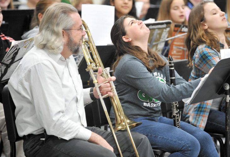 Dan Cassady, at left, the former Director of Bands at St. Edmond, sat in for a few minutes during a Karl King Honor Band at St. Edmond Catholic School to prank his friend Kathy Yoakam, of Humboldt, who was directing the group. Alex Tiernan, 11, reacts to his prank, center. Cassady will be the featured soloist at tonight's show.