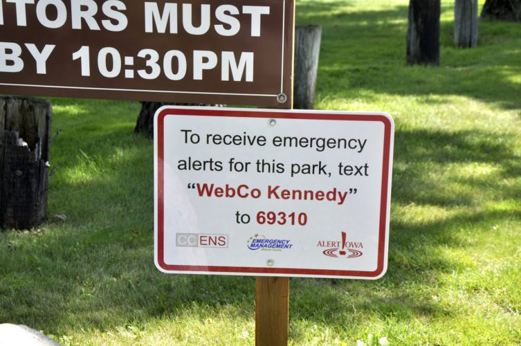 -Messenger photo by Peter Kaspari  A sign informing visitors how to sign up for emergency alerts was recently installed at John F. Kennedy Memorial Park. The number allows park visitors to receive alerts on their smartphones.