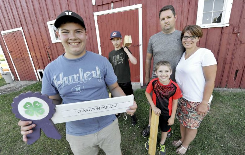 -Messenger photo by Hans Madsen  Christian Lundberg, 17, a member of the Gowrie Groundbreakers 4-H Club, holds up an old sign that he's replicating this year as his entry for the Webster County Fair. His parents, Matt and Brianne Lundberg, at right, were also both 4-H members in their youth. His youngest sibling, Riley Lundberg, 7, will be joining when he's old enough. Middle sibling Kadyn, 13, is also a member of the Gowrie Groundbreakers. The family can trace their involvement in 4-H six generations.