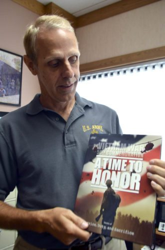 -Messenger photo by Joe Sutter  Webster County Veterans Affairs Director Dan Lewandowski holds the new Vietnam War commemorative books now available for free for all veterans of that war.