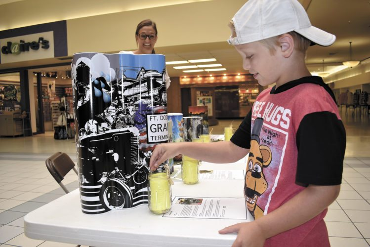 -Messenger photo by Chad Thompson  Nolan Naso, 8, of Kamrar, makes his pick for the Fort Dodge Grain Silo Mural project at Crossroads Mall Tuesday afternoon. Brooke Axness, an intern for the city of Fort Dodge, looks on. Votes are cast by placing a kernel of corn in a jar next to the silo of choice. A public open house was held Monday and Tuesday. Public voting will conclude today at Crossroads Mall. Naso voted for Brent Holland's work. Holland is an artist from Des Moines. The Public Art Committee has selected five semifinalists for the project. Rolf and Peter Goetzinger; Hannah Wilson, of Durango, Colorado; Guido Van Helten, of Australia; and Josh Johnson, of Fort Dodge; are the other finalists. The winner's artwork will be featured on the silo, located at the east bookend of the Northwest River District, along the Des Moines River.