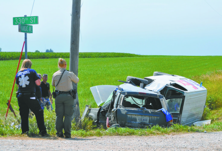 -Messenger photo by Peter Kaspari  Webster County Sheriff's Deputy Amy Stringer looks over the wreckage of a two-vehicle accident at 330th Street and Kansas Avenue, just west of U.S. Highway 169.