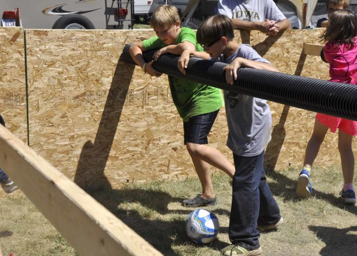 -Messenger photo by Peter Kaspari  Nathan Graves, 10, left, and Drew Lundgren, 10, both members of the Dayton Tigers 4-H club, prepare to kick the ball during a human foosball game at the Webster County Fair Friday.
