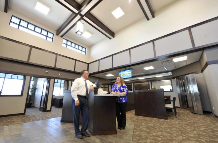 -Messenger photo by Hans Madsen  Heartland Bank President/CEO Kevin Black, at left, along with Ashley Hanson, loan administrative clerk, stand at the pod used by bank employees to help customers as they walk into the newly built building.
