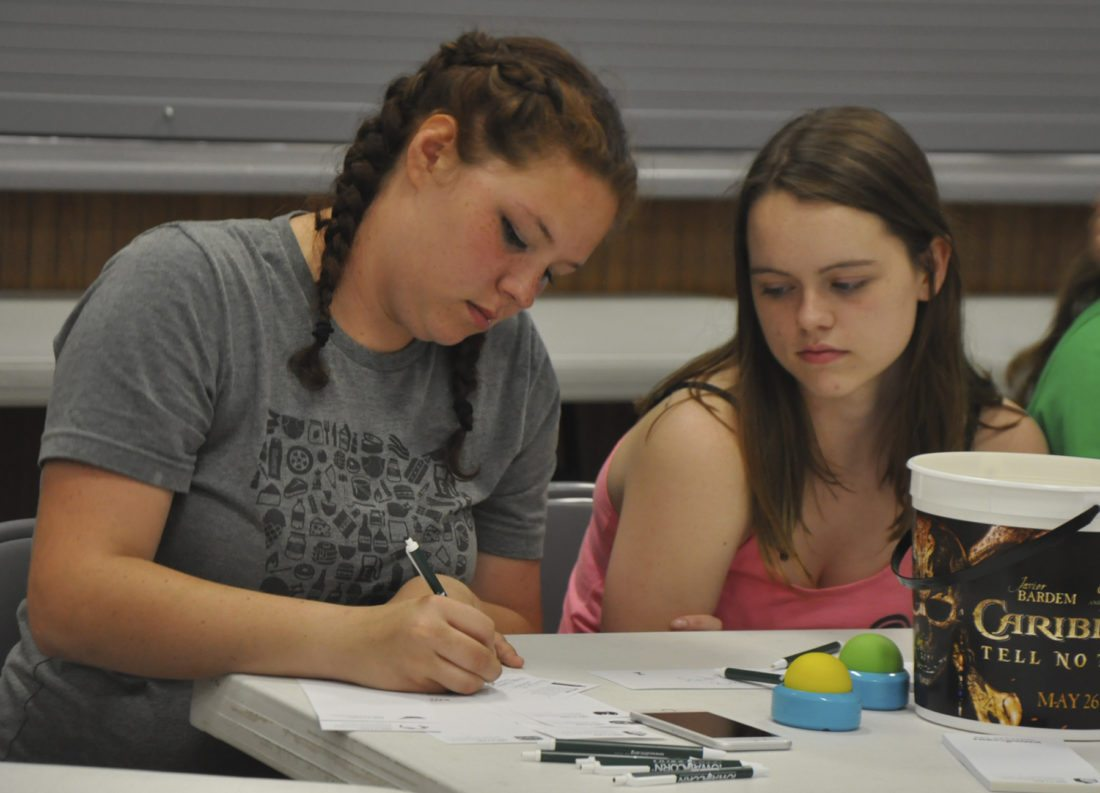 -Messenger photo by Peter Kaspari  Kacie Cox, 18, left, of Marathon, takes notes during the corn quiz bowl at the Pocahontas County Fair as Andrea Bennett, 18, of Pocahontas, looks on. Both are members of the Guys and Gals of Grant 4-H club.