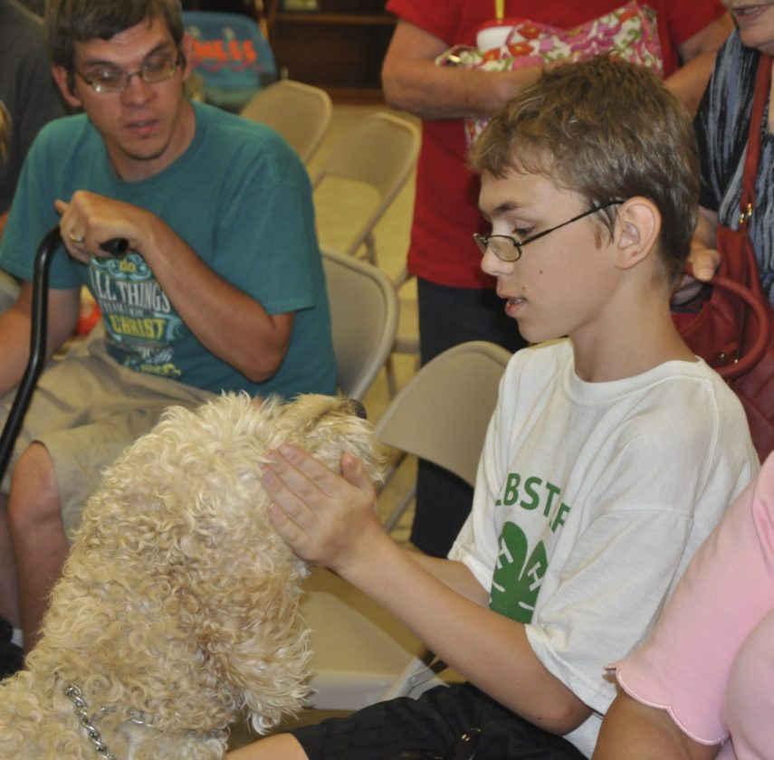 -Messenger photo by Peter KaspariRobbie Jasper, 14, a member of the C/C Sidekicks 4-H club, pets his Goldendoodle, Duke, shortly before showing him at the pet project during the Webster County Fair Sunday. Jasper tied for showmanship champion.