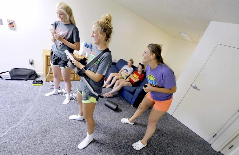 -Messenger photo by Hans Madsen  Teammates Emma Valainis, at left, Sophie VanSeveren and Nicole Timmons, right, share a laugh as they work to get their Wii game set up and running Wednesday afternoon in their dorm room at Iowa Central Community College where they staying during the Iowa High School Girls State Softball Tournament. The players, from Assumption, play for the Assumption Knights. Ally Courtney and Hannah Johnson enjoy a snack on the couch.