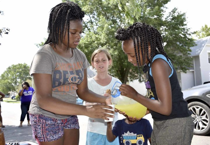 -Messenger photo by Chad Thompson  Janyla Manard, 9, of Fort Dodge, right, pours some lemonade with the help of Makyia Thomas, 12, along Fourth Avenue South Wednesday afternoon. Alyssa Hopen, 10, center, looks on. With temperatures on the rise, the three girls started a lemonade stand on Tuesday. Thomas said they have been using the money they earn to buy more supplies for their stand.