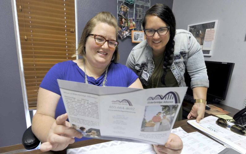 -Messenger photo by Hans Madsen  Elderbridge Agency on Aging marketing assistant Jennifer Brown, at left, along with Elderbridge Alliance program coordinator Amber Hobson, right, look over a brochure explaining the new programs being offered by the Elderbridge Alliance.