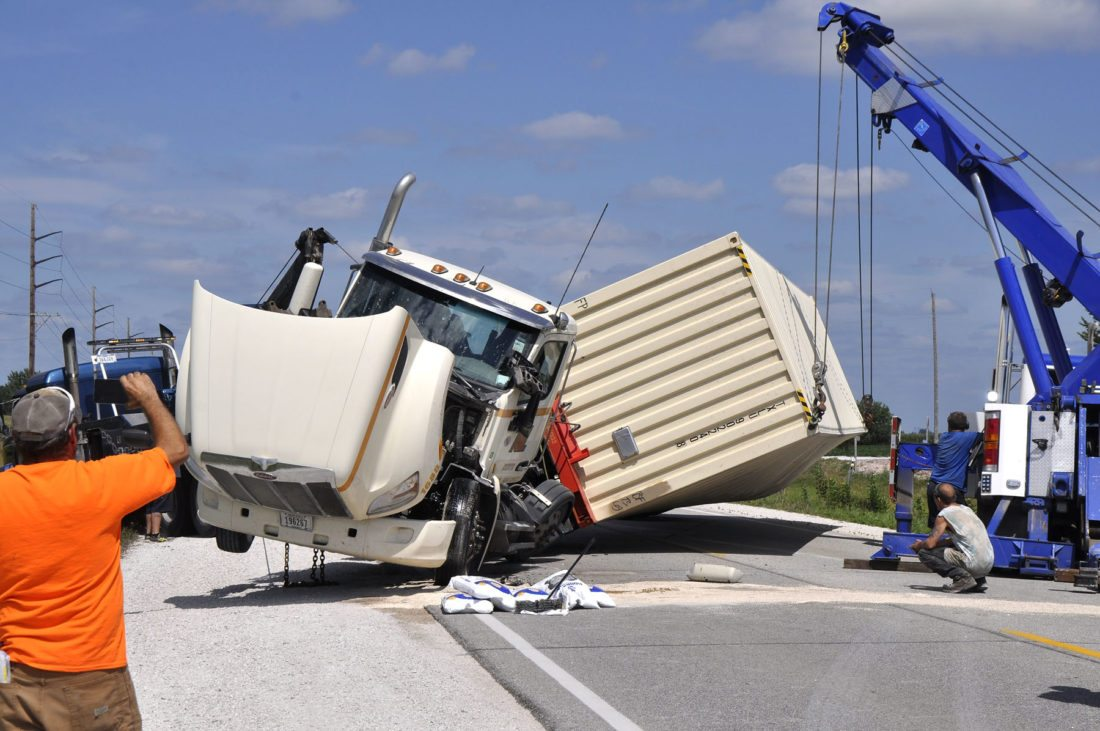 -Messenger photo by Joe Sutter  A tow truck and crane from MidIowa Towing carefully lift this semi upright after it overturned on Old Highway 20 Monday afternoon southwest of Fort Dodge. The road was closed for more than half an hour.