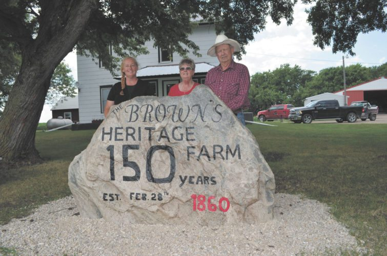 -Messenger photo by Kriss Nelson Dawn Fedkenheuer stands with her parents, Coco and Tom Brown, by a rock that Fedkenheuer painted to commemorate their family's Heritage Farm. The Brown Heritage Farm was established Feb. 28, 1860, by Thomas Brown, Tom's great-grandfather.
