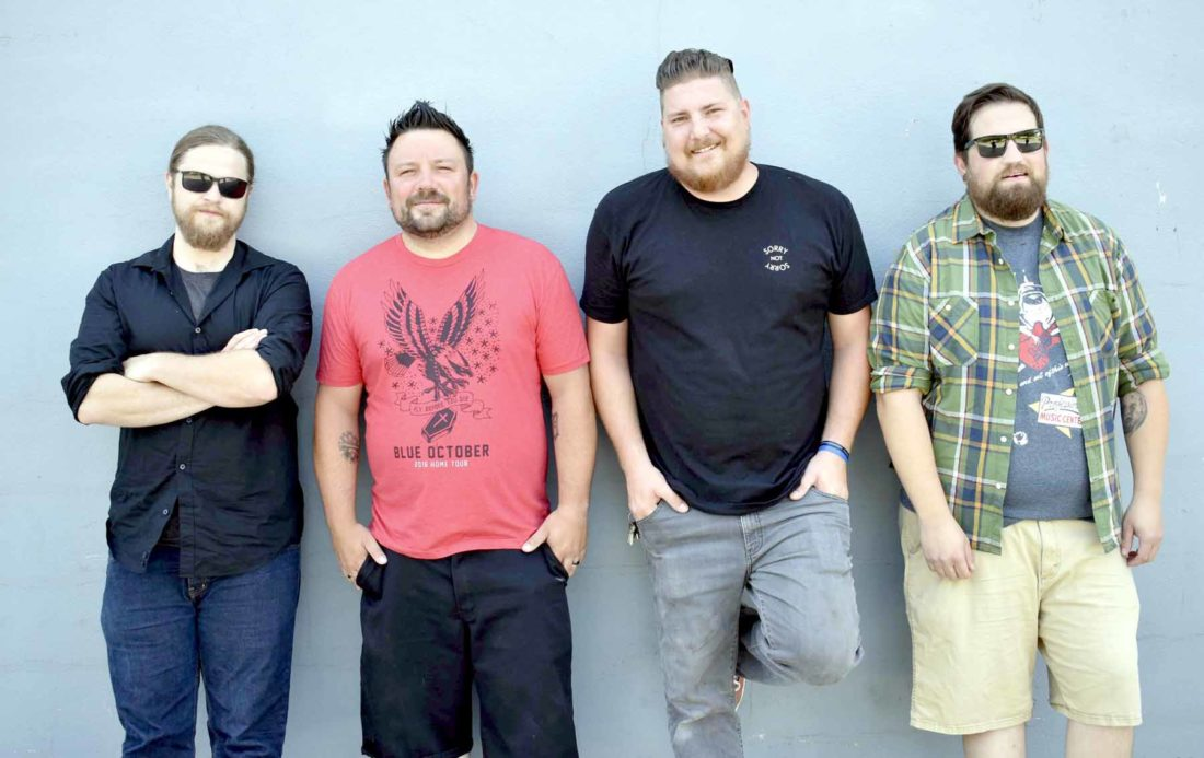 -Messenger photo by Chad Thompson  Riddled With Class, an area cover band, pose together outside of a building in Rockwell City recently. From left to right: Jake Merritt, of Manson, Nick Ehrhardt, of Humboldt, Levi Drew, of Rockwell City, and Greg Merritt, of Manson.