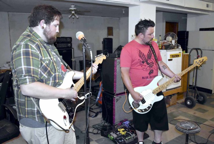 -Messenger photo by Chad Thompson  Greg Merritt, of Manson, on guitar, left, and Nick Ehrhardt, of Humboldt, on bass, perform together recently in Rockwell City. Their band, Riddled With Class, is playing at The Pour House in Humboldt Aug. 5.