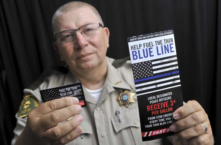 "-Messenger photo by Hans Madsen  Webster County Sheriff Jim Stubbs holds up a sample Star Energy ""Help Fuel the Thin Blue Line,"" card and the brochure explaining their use. Proceeds in Webster County go the Webster County Crime Stoppers."