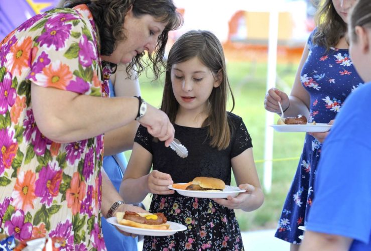 -Messenger photo by Hans Madsen  Maureen Hans, of Ankeny, at left, makes sure her daughter, Peyton Hans, 11, has enough carrot sticks Friday evening to go with her pork loin sandwich at the 8th annual Legends Tailgate at Friendship Haven.
