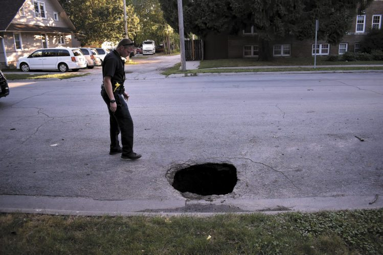 -Messenger photo by Chad Thompson  Officer Troy Kleppe, of the Fort Dodge Police Department, looks over a sinkhole that developed along South 17th Street Thursday. The hole appeared to be about 4 feet wide. The estimated depth of the hole was about 20 feet deep. The road was not blocked off Thursday night. Traffic cones were to be placed around the hole. No injuries were reported.