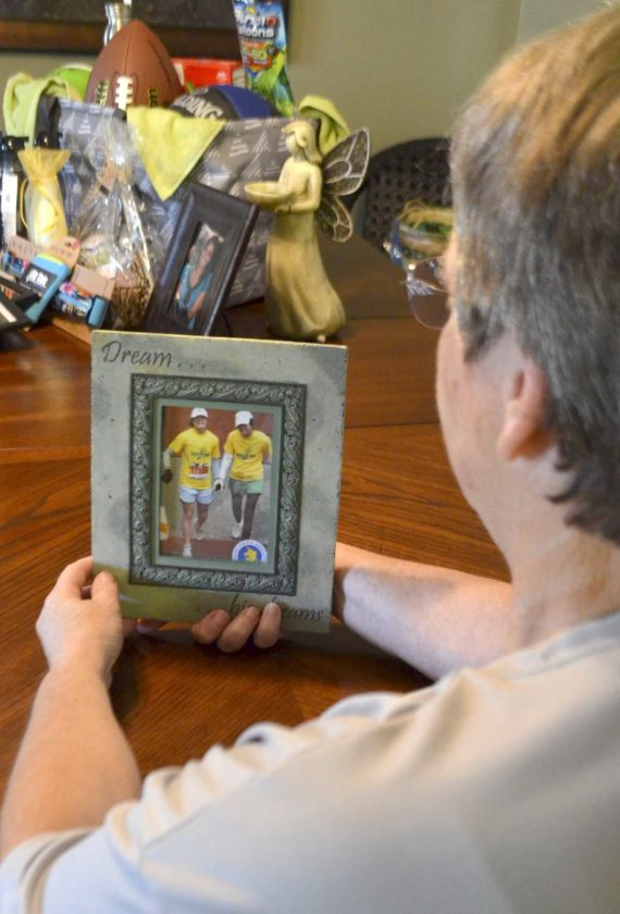 -Messenger photo by Joe Sutter  Betty Sweet looks at a photo of her daughter Abby finishing the Boston Marathon with Emily Markert in 2007, about a year after Markert had a lung transplant. Markert passed away in  2014, and the annual run to honor her and raise awareness of organ donation will be Aug. 12.