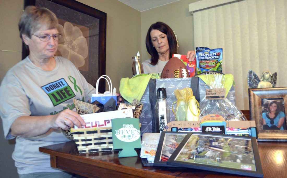 -Messenger photo by Joe SutterBetty Sweet, left, and Liz Markert arrange a collection of raffle prizes that will be given out during Emily's FightÑDonate life run/walk fundraiser. A photo of Emily Markert sits at right.